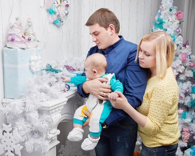 Liefhebbende ouders tonen hun baby kerstcadeaus. het concept van kerstmis