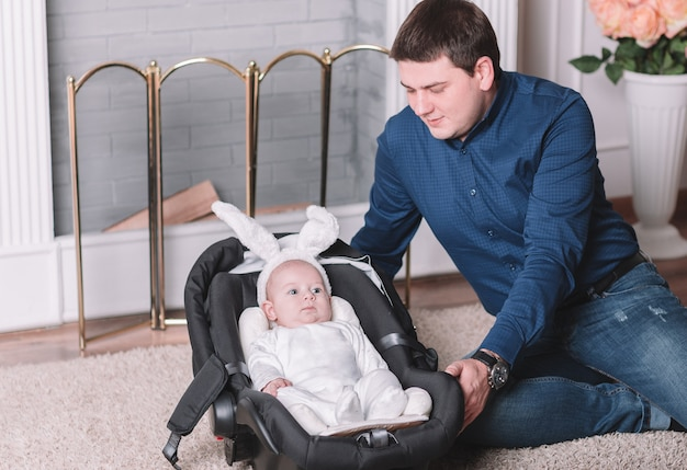 Liefhebbende vader en een mooie baby in een konijnenkostuum voor een wandeling