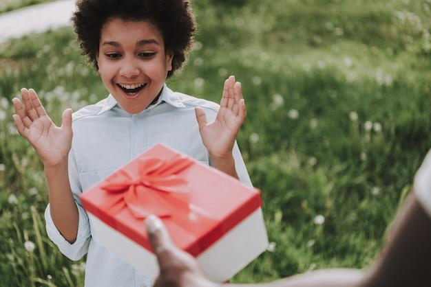 Liefhebbende vader geeft cadeau en verrast jongen glimlachen.