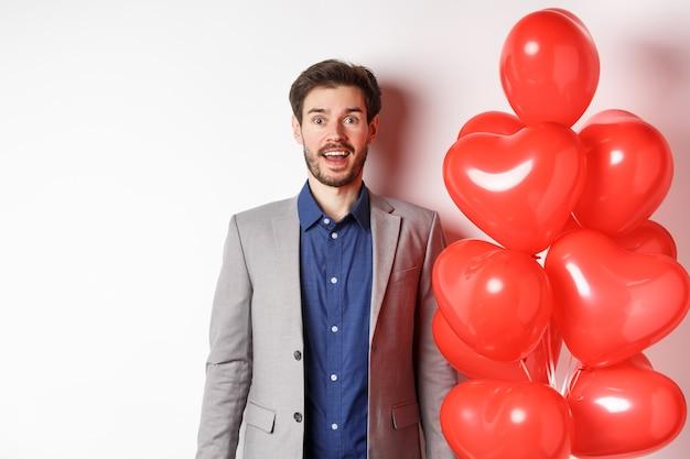 Liefhebbers dag. opgewonden knappe man in pak staande in de buurt van rode harten ballonnen, wenkbrauwen optrekken en verbaasd kijken, staande op een witte achtergrond.
