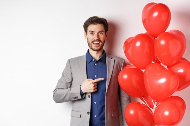 Liefhebbers dag. opgewonden mannelijk model in pak wijzende vinger naar valentijnsdag hart ballonnen en glimlachen, romantische geschenken voorbereiden op datum, staande op witte achtergrond.