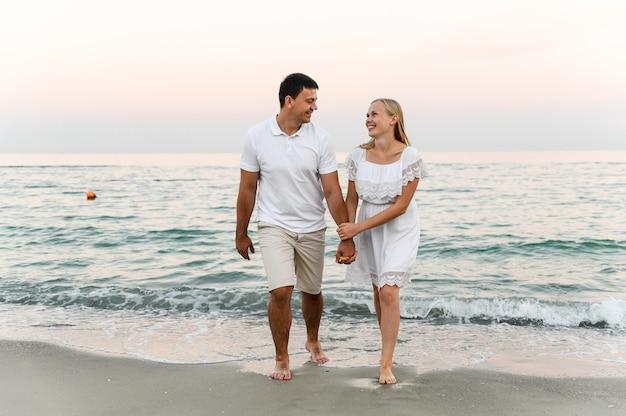 Liefhebbers in de buurt van de oceaan knuffelen en hebben plezier. man en vrouw knuffels bij zonsondergang in de buurt van de zee.