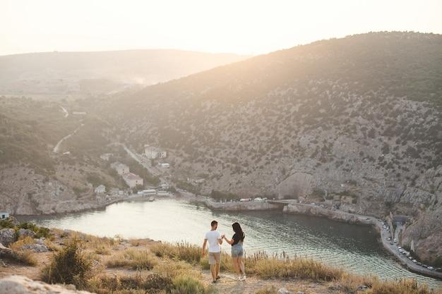 Liefhebbers, jongen en meisje, aan de rand van de klif tegen de achtergrond van bergen en oceaan.