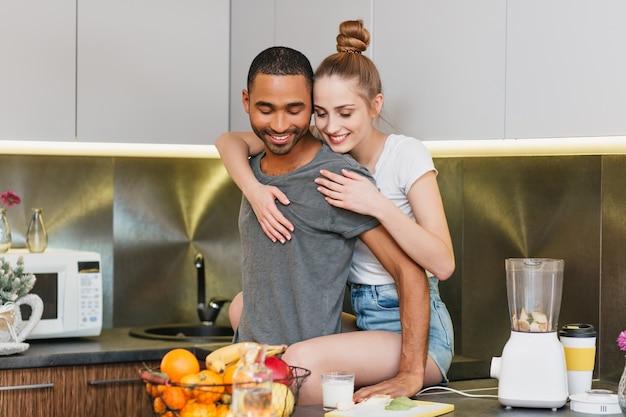 Liefhebbers knuffelen in de keuken, houden van sfeer. paar flirten in een huiskleren. zachte ogen, warme relatie.