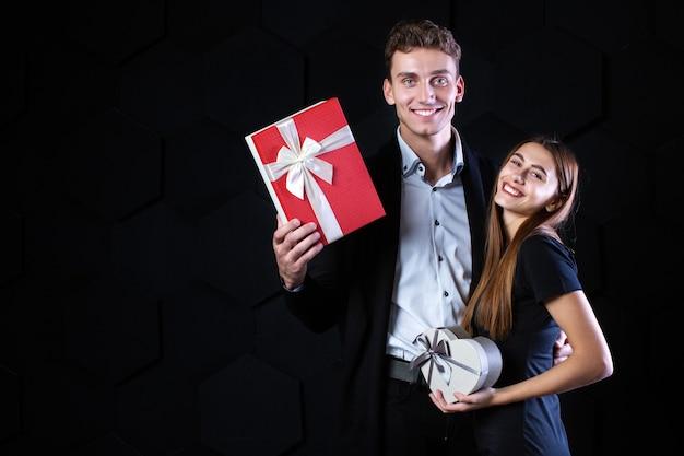 Liefhebbers met geschenken lachen en plezier, kijkend naar de camera. viering en romantisch concept.