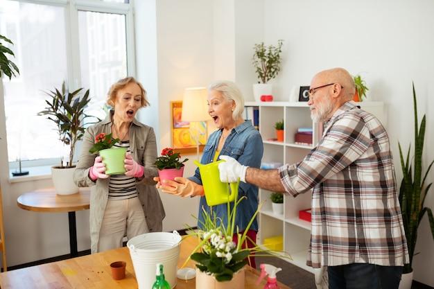Liefhebbers van bloemen. leuke opgewonden vrouwen die glimlachen terwijl ze hun bloempotten vasthouden
