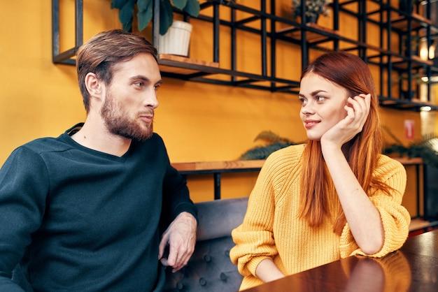 Liefhebbers van man en vrouw aan een tafel in de familie van een café-communicatie vrienden