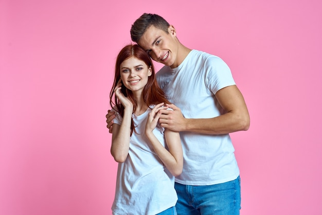 Liefhebbers van man en vrouw in spijkerbroek en t-shirt op roze achtergrond bijgesneden weergave.