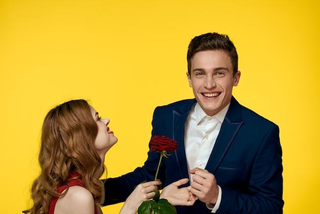 Liefhebbers van man en vrouw met een rode roos in hun handen knuffelen op een gele achtergrond
