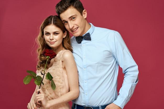 Liefhebbers van mensen met roos in handen op roze geïsoleerde ruimte knuffel emoties geluk romantiek gevoelens