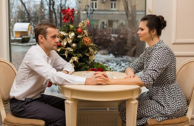 Liefhebbers zitten op date aan een tafel in een café