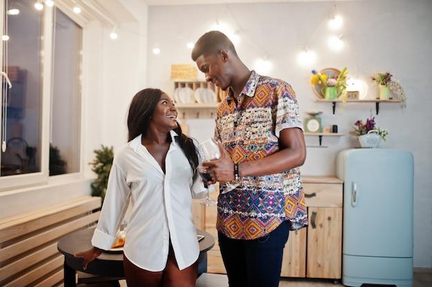 Liefjes die van het afro het amerikaanse paar wijn in keuken drinken op hun romantische datum.
