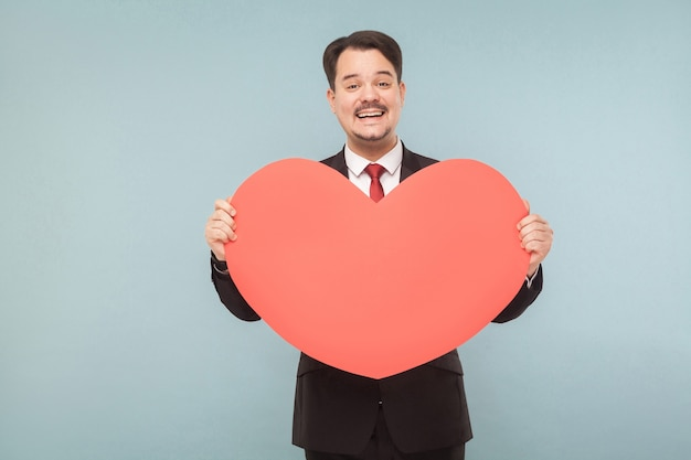 Liefs, st. valentijnsconcept. man toothy glimlachen, met een groot hart. binnen, studio-opname, geïsoleerd op lichtblauwe of grijze achtergrond