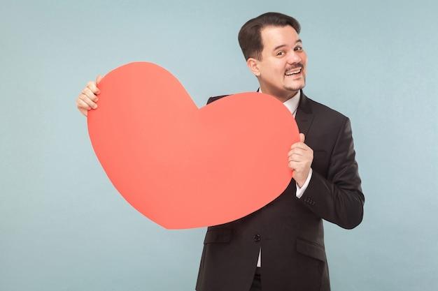 Liefs, st. valentijnsconcept. zakenman met groot hart, brede glimlach. binnen, studio-opname, geïsoleerd op lichtblauwe of grijze achtergrond