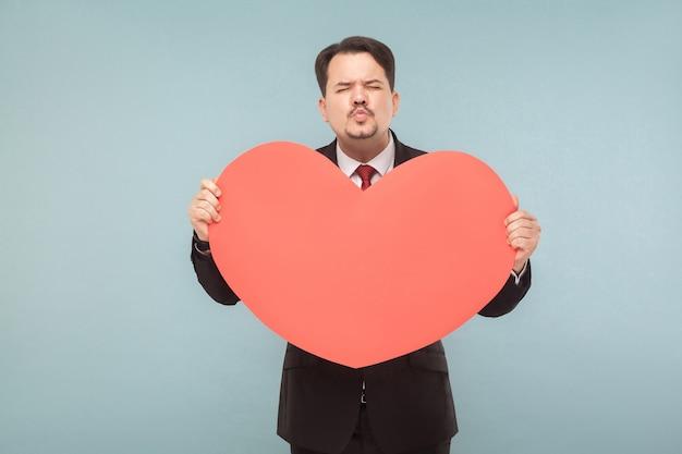 Liefs, st. valentijnsconcept. zakenman met groot hart, stuur kus. binnen, studio-opname, geïsoleerd op lichtblauwe of grijze achtergrond