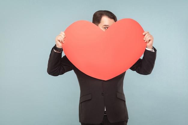 Liefs, st. valentijnsconcept. zakenman met groot hart, zorgen, paniek. binnen, studio-opname, geïsoleerd op lichtblauwe of grijze achtergrond