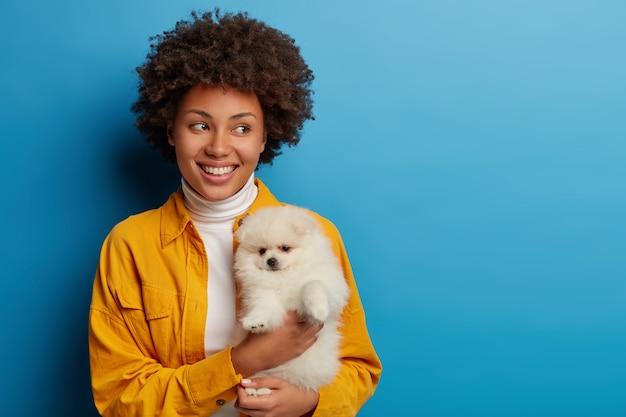 Lieftallige gastvrouw met gekruld haar draagt witte spits, geniet van leuke tijd met een trouwe huisdieren, kijkt glimlachend opzij, speelt met huisdier, draagt geel shirt