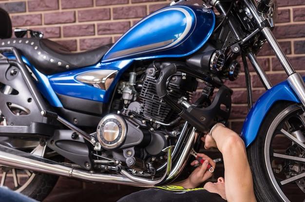 Liegende man die sommige delen van zijn sportmotorfiets handmatig thuis repareert.