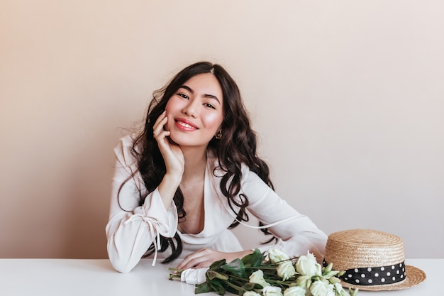 Lieve aziatische vrouw die met krullend haar bij camera glimlacht. studio shot van charmant japans model met witte bloemen.