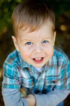 Lieve babyjongen, close-up portret van kind geïsoleerd op hout achtergrond, schattige peuter met blauwe ogen