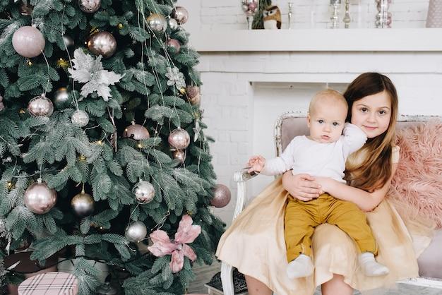 Lieve blanke broers en zussen, baby en een meisje, bij de kerstboom