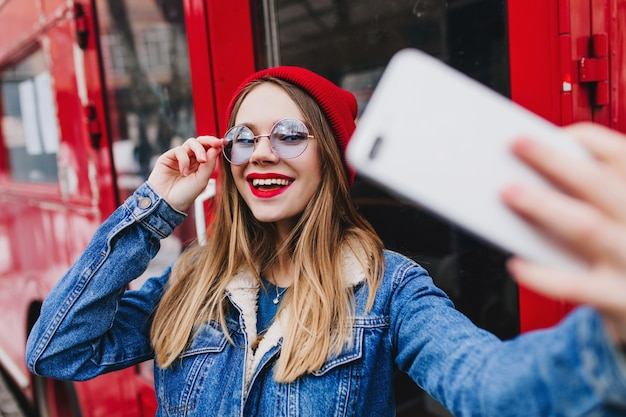 Lieve blanke vrouw speels haar bril aan te raken tijdens het maken van selfie in de buurt van bus.