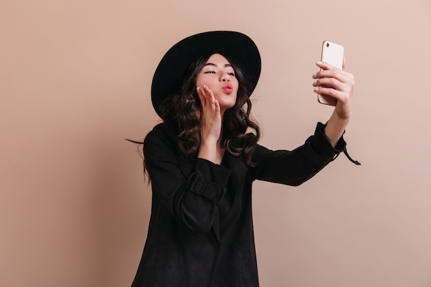 Lieve chinese dame selfie te nemen. winsome aziatische vrouw met smartphone poseren op beige achtergrond.