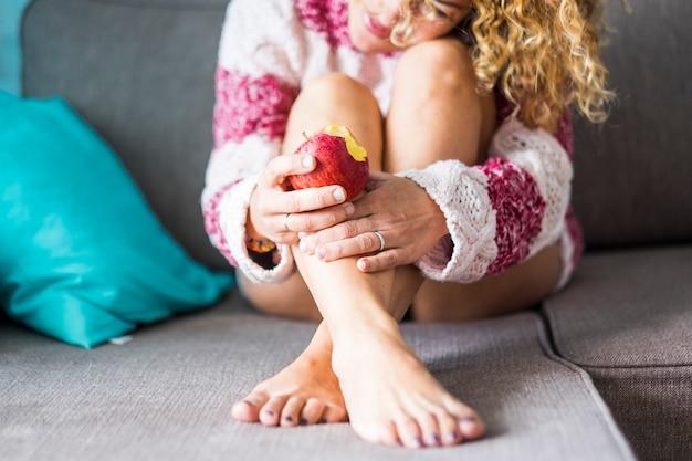 Lieve en tedere eenzame blanke dame die thuis op de bank zit en een gezonde rode appel eet