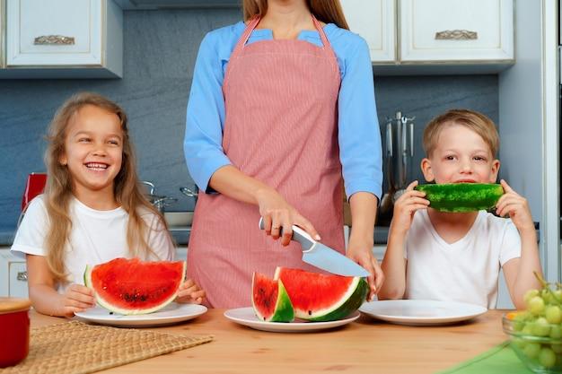 Lieve familie, moeder en haar kinderen die watermeloen eten in hun keuken met plezier