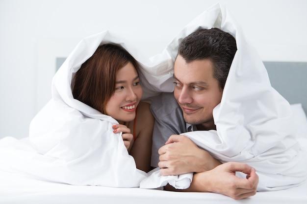 Lieve jonge pasgetrouwden die in hotelkamer rusten