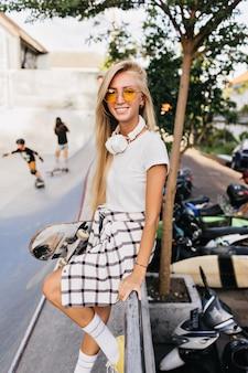 Lieve jonge vrouw in gele zonnebril poseren op straat achtergrond met verlegen glimlach.