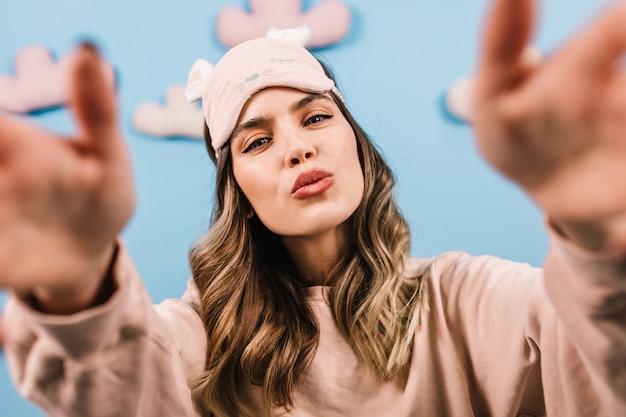 Lieve jonge vrouw in slaapmasker selfie maken