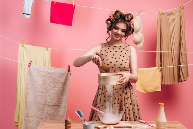 Lieve, jonge vrouw maakt eten klaar, ze zeeft bloem door een zeef. mooie huisvrouw is bezig met huishoudelijke taken op een roze achtergrond.