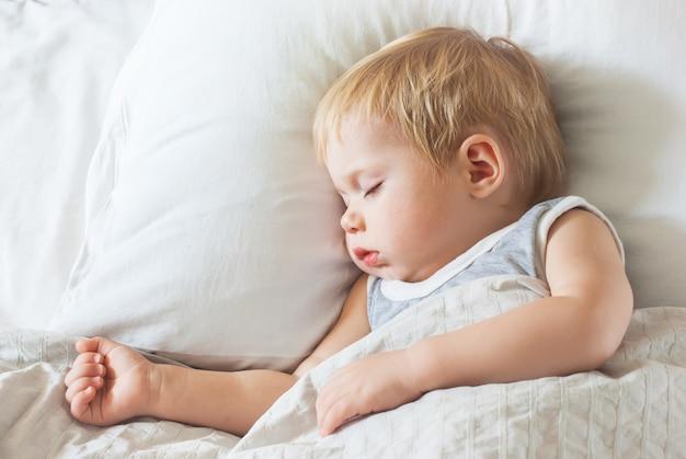 Lieve jongen slaapt op bed