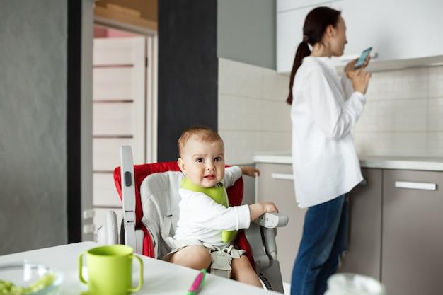 Lieve kleine baby in groene slabbetje zittend in een kinderstoel wordt bang om vogel buiten het raam te zien, terwijl moeder opzij draait om chatrooms op smartphone te controleren.