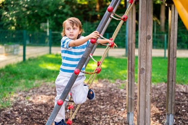 Lieve kleine jongen spelen in een park op speelplaats. peuter die wegkijkt en een glijbaan beklimt. zomeractiviteiten voor kinderen.