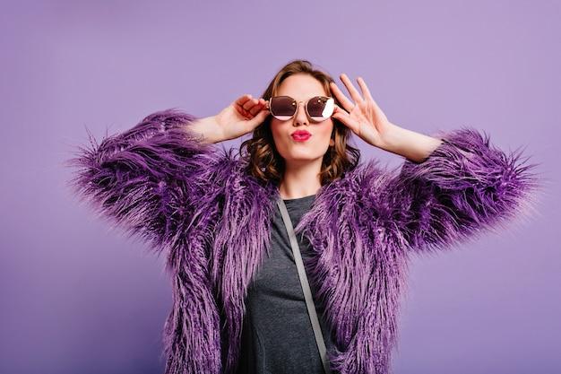 Lieve kortharige vrouw in stijlvolle paarse jas gelukkige emoties uitdrukken