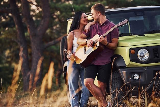 Lieve mensen staat in de buurt van groene jeep met alcohol en akoestische gitaar