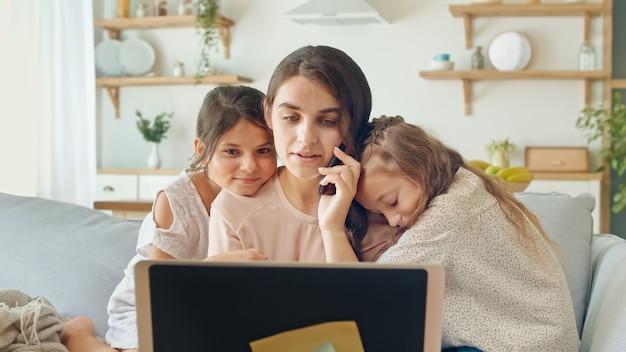 Lieve moeder die op afstand werkt vanuit huis terwijl ze kinderen knuffelt, moeder aait een dochter