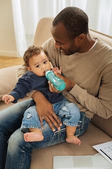 Lieve schat. aantrekkelijke uitbundige donkerogige bebaarde afro-amerikaanse man die lacht en zijn kind voedt terwijl hij zijn zoon op schoot houdt