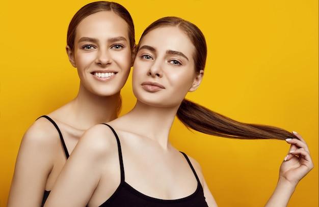 Lieve twee blanke meisjes die positieve emoties uitdrukken