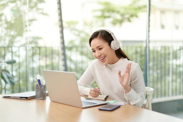 Lieve vrouw die op laptop met hoofdtelefoon op haar hoofd werkt