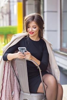 Lieve vrouw scrollen smartphone tijdens het rusten in de stad