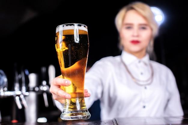 Lieve vrouwenbarman demonstreert zijn professionele vaardigheden terwijl hij naast de bar in de bar staat