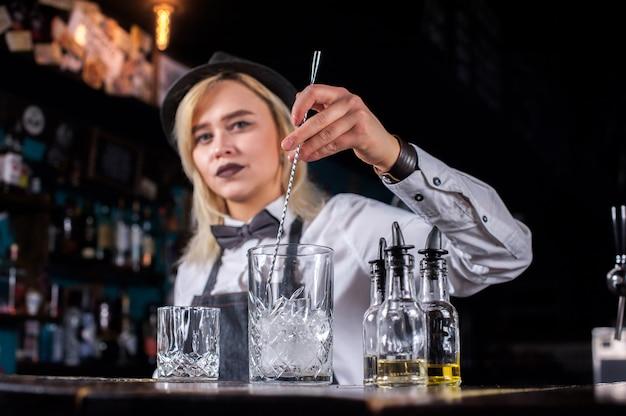 Lieve vrouwenmixoloog verrast met zijn vaardigheidsbarbezoekers terwijl ze naast de bar in de bar staat