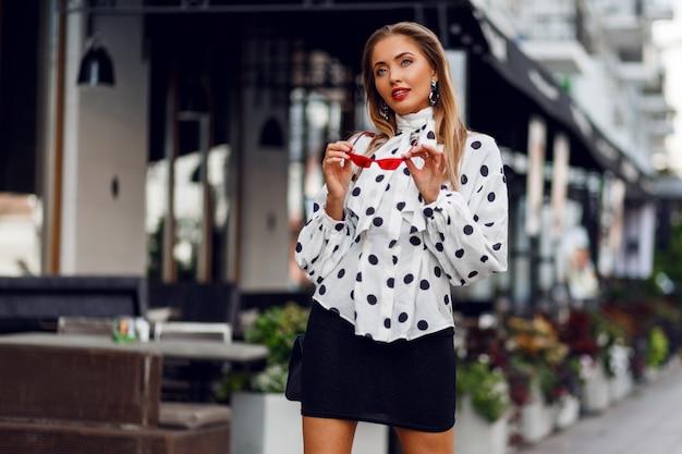 Lieve zelfverzekerde blonde vrouw met lang kapsel poseren op straat over moderne café