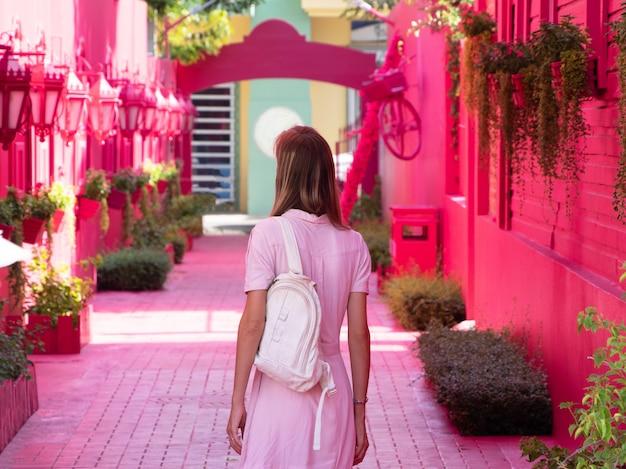 Lifestyle afbeelding. aantrekkelijke vrouw loopt langs een roze steegje. gekleed in een roze jurk. de toeristische straat is roze.