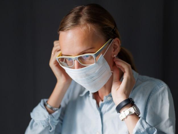 Lifestyle afbeelding. het mooie wijfje dat medisch masker thuis zet alvorens gaat op het werk. close-up shot. bescherm coronavirus. selectieve aandacht. covid-19 concept