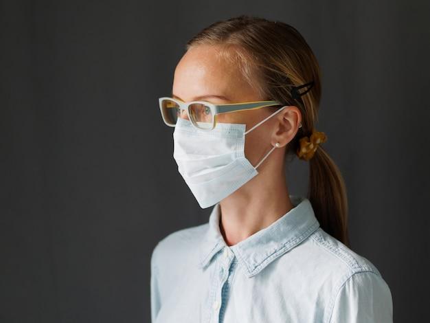 Lifestyle afbeelding. portretvrouw die chirurgisch medisch masker voor coronavirus dragen. covid-19 concept