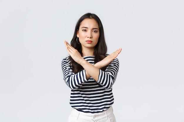 Lifestyle, beauty en mode, mensen emoties concept. serieus ogende ontevreden aziatische vrouw zegt dat ze moet stoppen, een kruisteken in een verbod laat zien, actie afkeurt, een waarschuwing geeft of iemand in bedwang houdt.